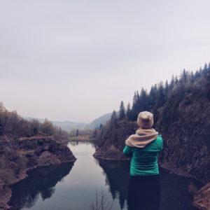Frau mit Blick auf einen Fluss und Berge